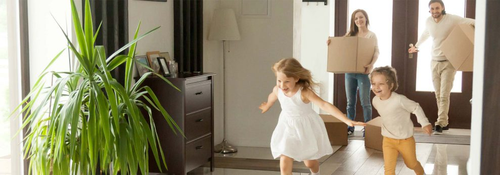 kids running through empty house as parents hold moving boxes